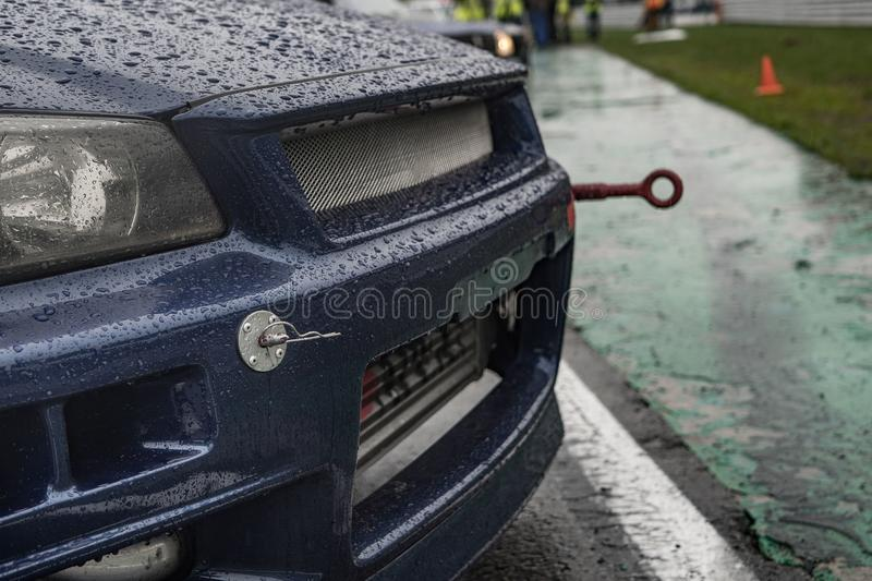 Hood of a blue sports car in front of a drift race. Rain royalty free stock image