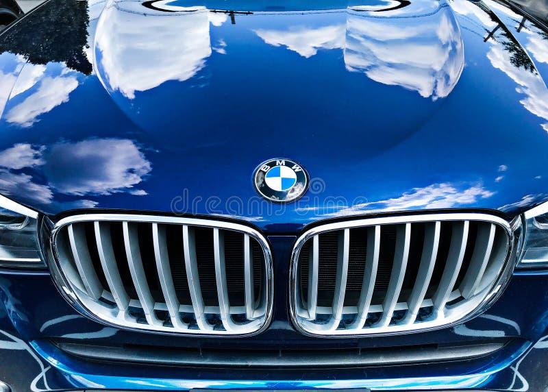 Капот внедорожника BMW. Баскинг-Ридж, Нью-Джерси, 08/03/2019: пасмурное небо отражается в капоте синего BMW стоковая фотография