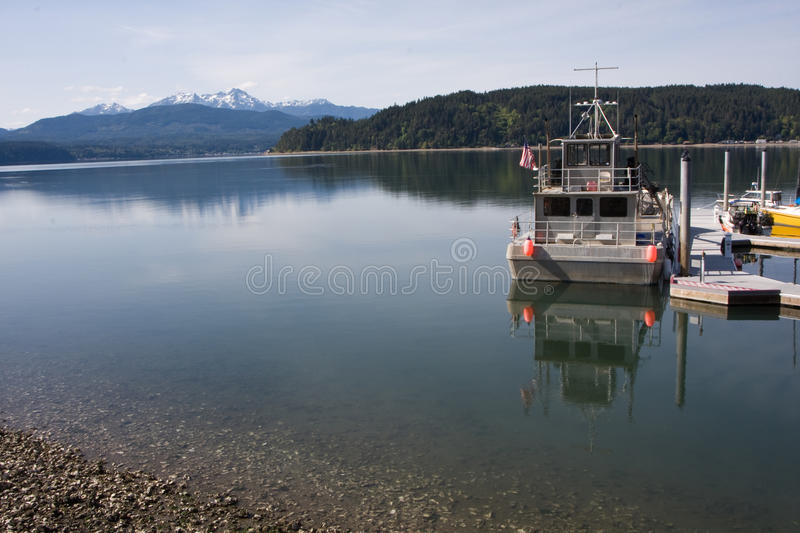 Hood Canal Washington with Olympic Mountains. Horizontal Photo of the Hood Canal in Washington State with Olympic Mountains in background and docked boat royalty free stock images