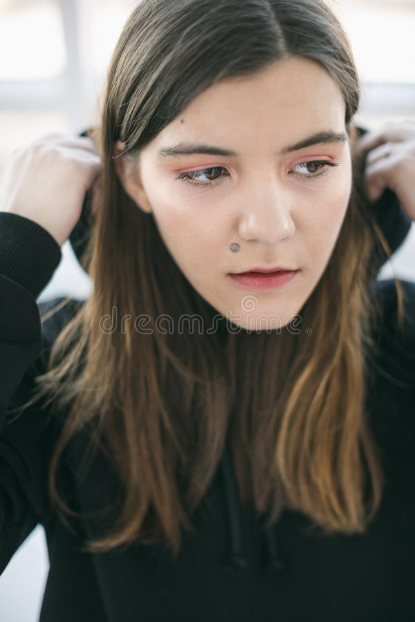 Hood wearing girl portrait. Close up. Beautiful face. Mole on the face royalty free stock photo