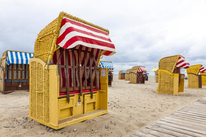 Hooded beach chairs strandkorb at Baltic seacoast in Travemunde, Germany. Strandkorb - colorful striped wooden hooded beach chairs. Sandy Baltic beach in royalty free stock photo