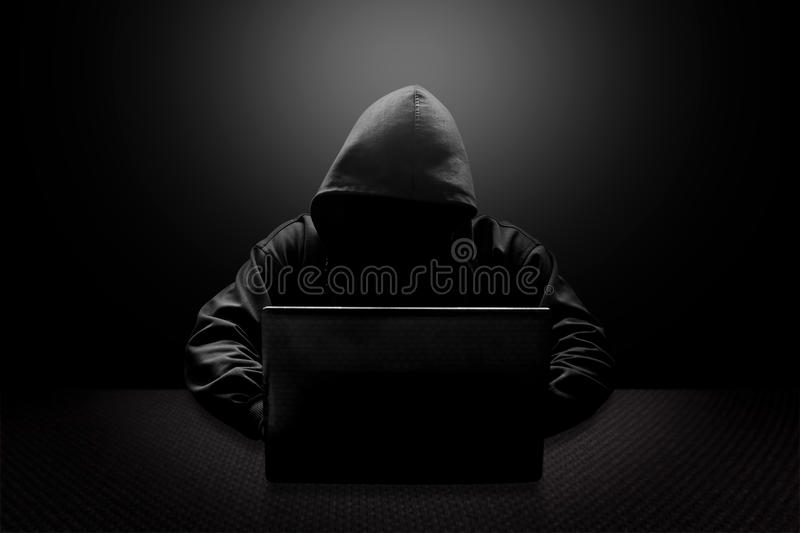 Hooded computer hacker stealing information royalty free stock photos