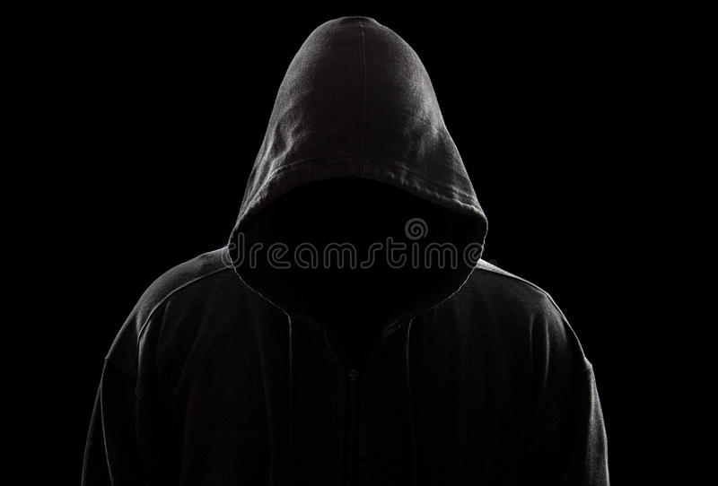 Hooded Figure. A dark and sinister figure in a hood against black royalty free stock photo