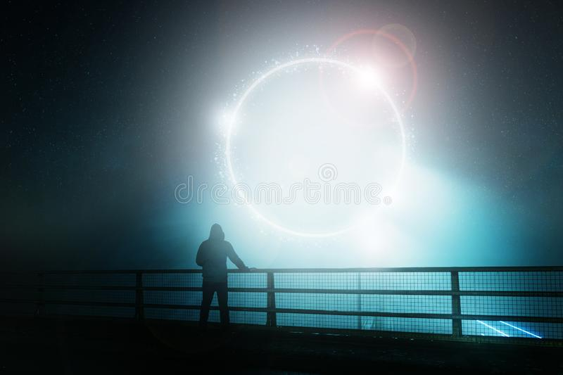 A hooded figure, standing with back to camera on a bridge, looking at a glowing, mystic, science fiction portal. On a foggy night.  royalty free stock images