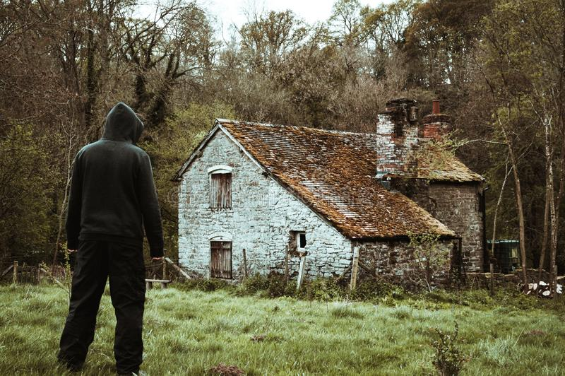 A hooded figure standing outside of an abandoned barn in the countryside in winter, with a cold, vintage edit stock images