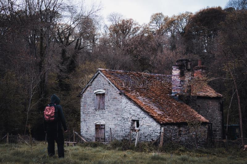 A hooded figure standing outside of an abandoned barn in the countryside in winter, with a cold, vintage edit stock photography