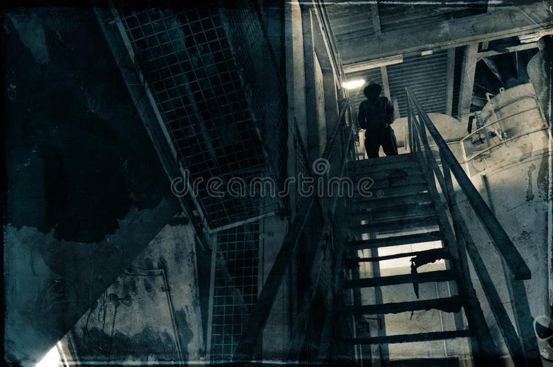 A hooded figure, standing on top of a metal staircase, in an abandoned industrial building. With a grunge vintage edit stock photos
