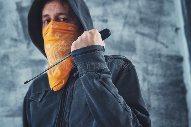 Hooded gang member criminal with screwdriver royalty free stock image