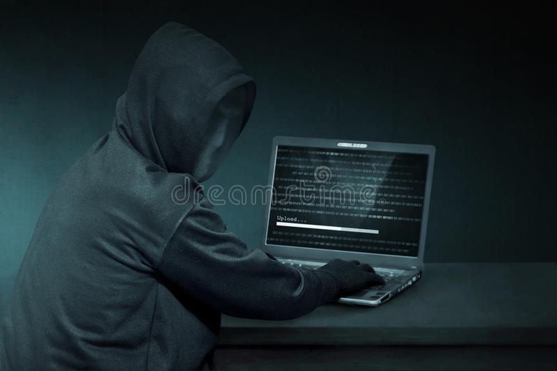 Hooded hacker with anonymous mask using laptop to steal data. In the dark room royalty free stock images
