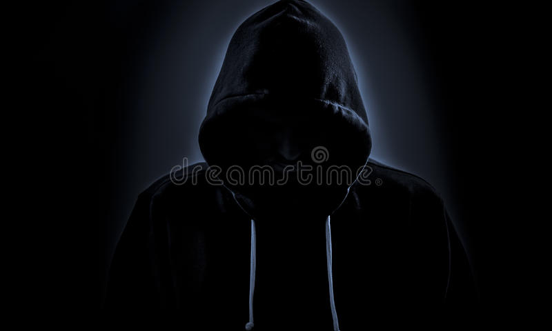 Hooded hacker in dark stock photo