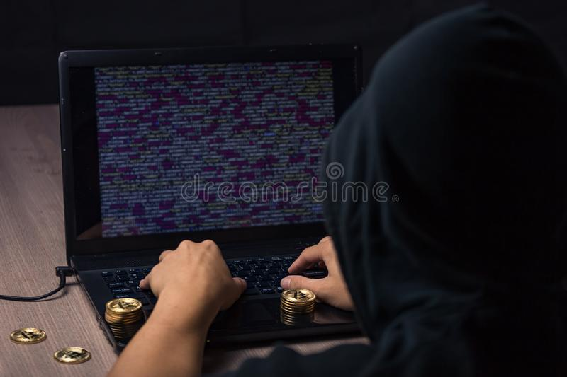 Hooded hacker using laptop to steal bitcoin stock image