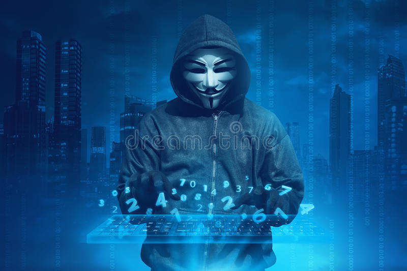 Hooded man with anonymous mask hacking system online security. Against concept background royalty free stock images