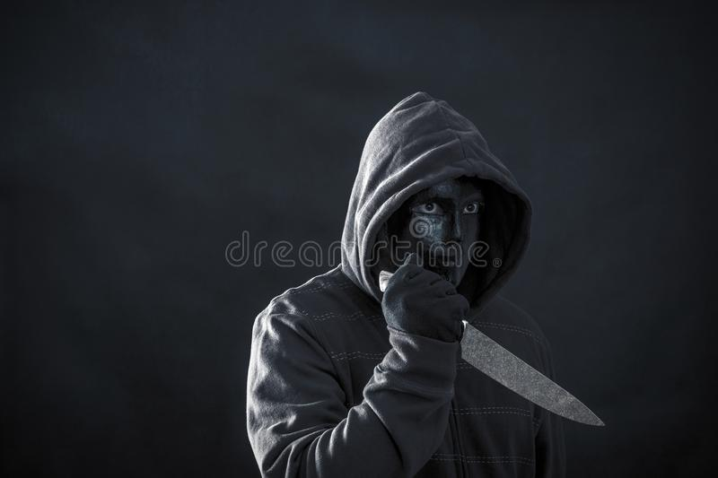 Hooded man with black mask holding knife stock photos