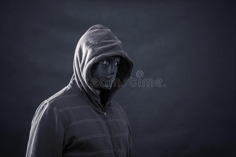 Hooded man with black mask stock image