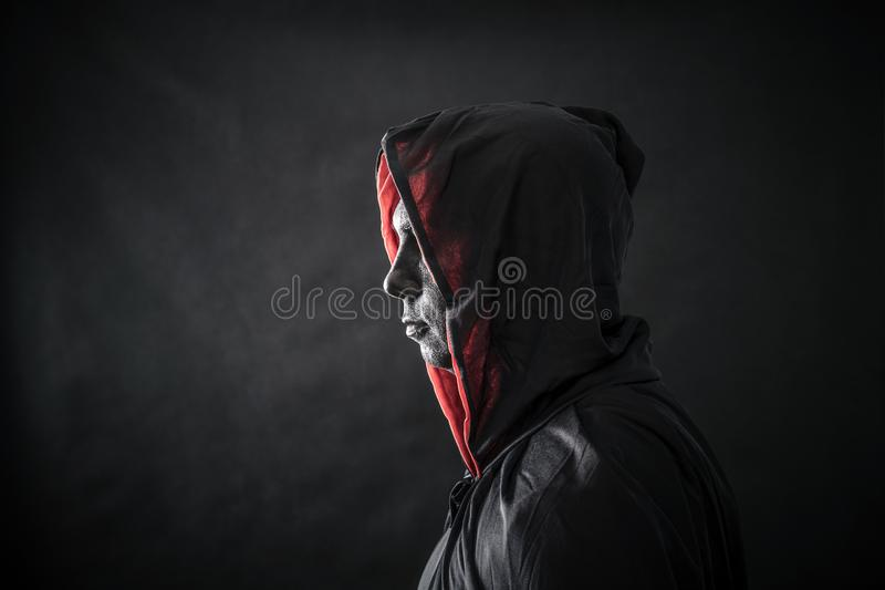 Hooded man in the dark stock images