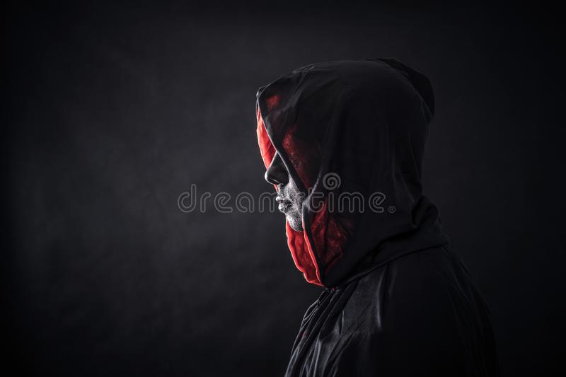 Hooded man in the dark royalty free stock photo