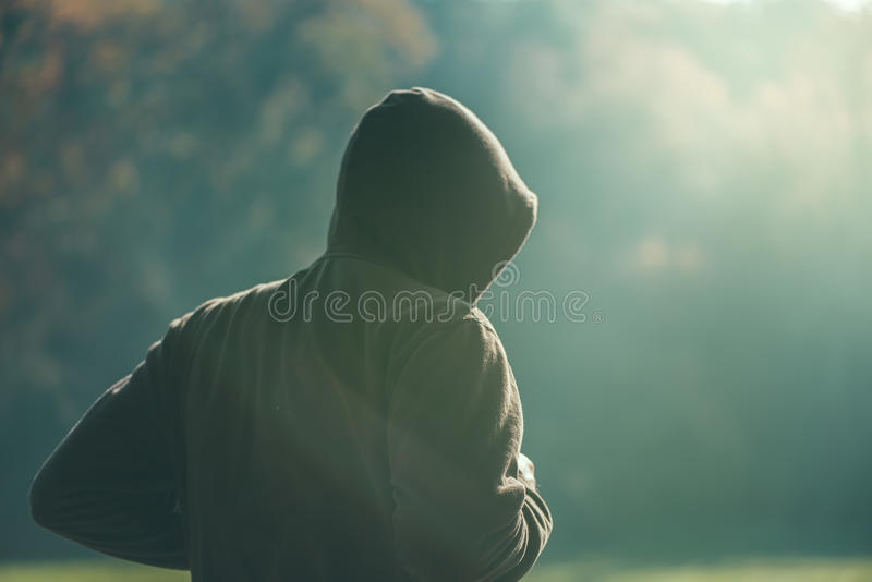 Hooded man jogging in the park in early autumn morning. Sport, recreation and healthy lifestyle concept, retro toned image with selective focus stock photos