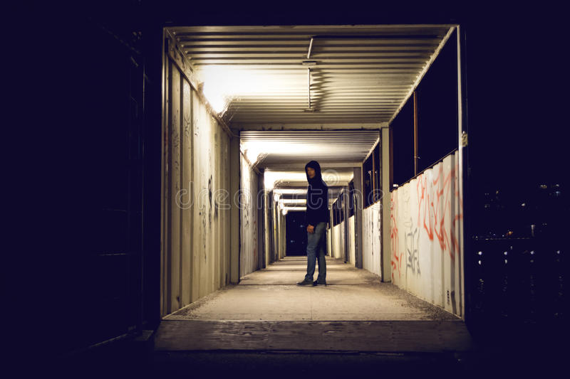 Hooded man standing in construction passage at night. Hooded man standing in a construction passage in a city at night. Cobwebs covering the lights royalty free stock image