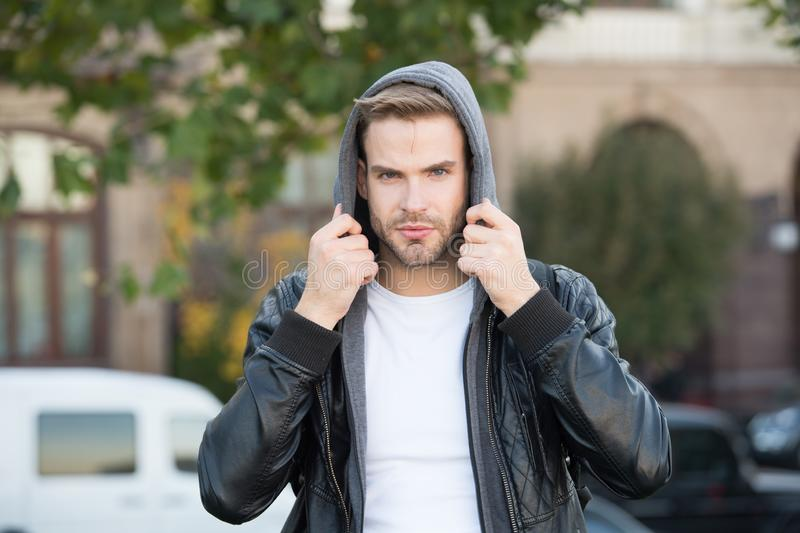 Hooded and protected. Handsome man unshaven face and stylish hair. Caucasian man urban background. Bearded man leather stock photo