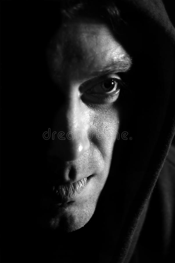 Hooded shadowed man stock image