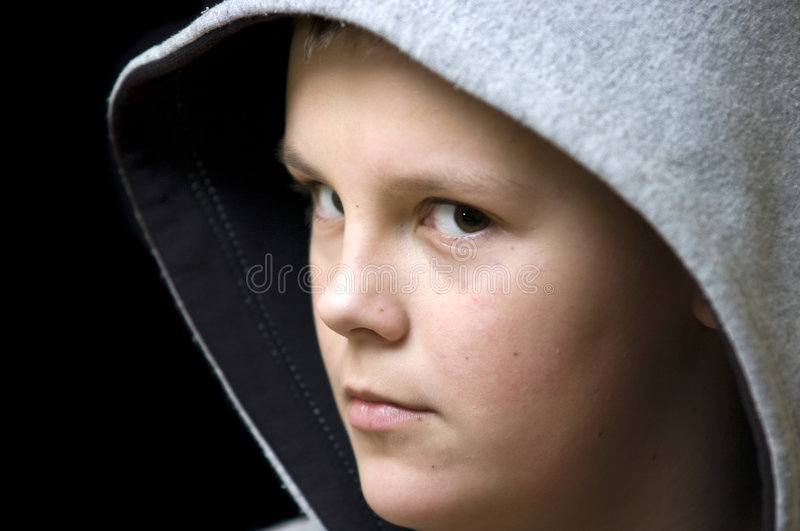 Hooded teenage boy. Portrait of a young teenage boy wearing a hood, isolated on black background. Serious expression on his face royalty free stock images