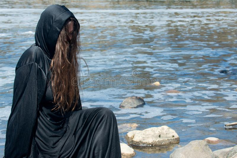 Hooded Woman with dark long hair in black robes in front of the Lake. Witches. Halloween and Gothic. Witchcraft and magic. stock photography