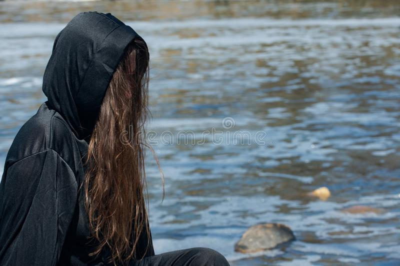 Hooded Woman with dark long hair in black robes in front of the Lake. Witches. Halloween and Gothic. Witchcraft and magic. stock photo