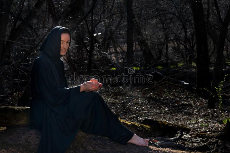 Hooded Woman with dark long hair in black robes sitting on a tree trunk in the forest. Back to Nature concept. Witchcraft royalty free stock photos