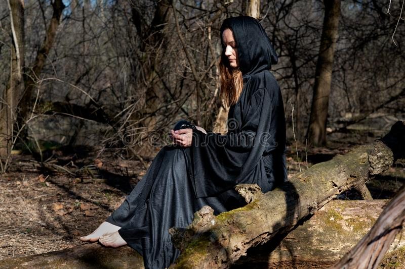 Hooded Woman with dark long hair in black robes sitting on a tree trunk in the forest. Back to Nature concept. Witchcraft stock photos