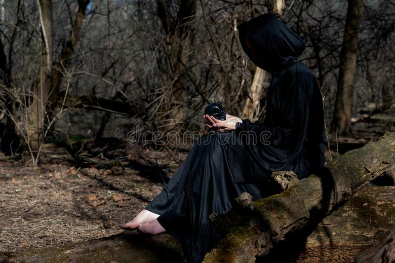 Hooded Woman with dark long hair in black robes sitting on a tree trunk in the forest. Back to Nature concept. Witchcraft stock image