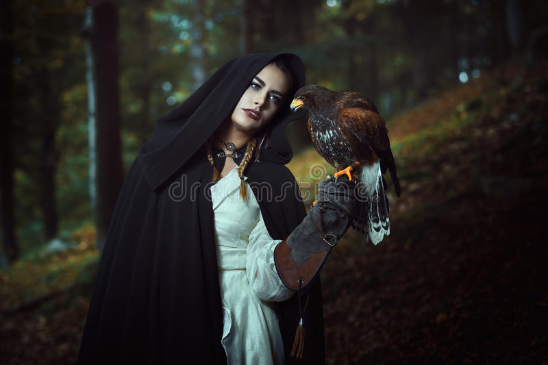 Hooded woman with hawk in dark woods stock image