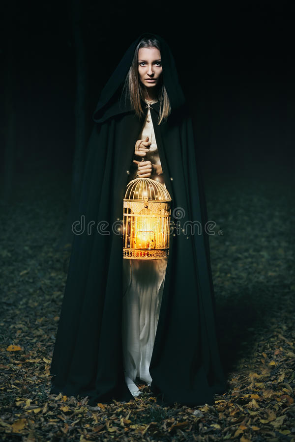 Hooded woman with lantern. Beautiful hooded woman with lantern of wisdom in dark forest. Fantasy and mythology stock photos