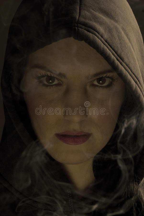 Hooded woman in night with fume. Portrait of hooded woman in night with fume around her,check also