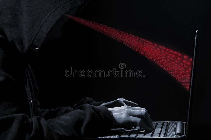 Hoodie Hacker!. Concept photo of a computer hacker in a hoodie with numbers - 1 and 0, coming out of the screen royalty free stock photography