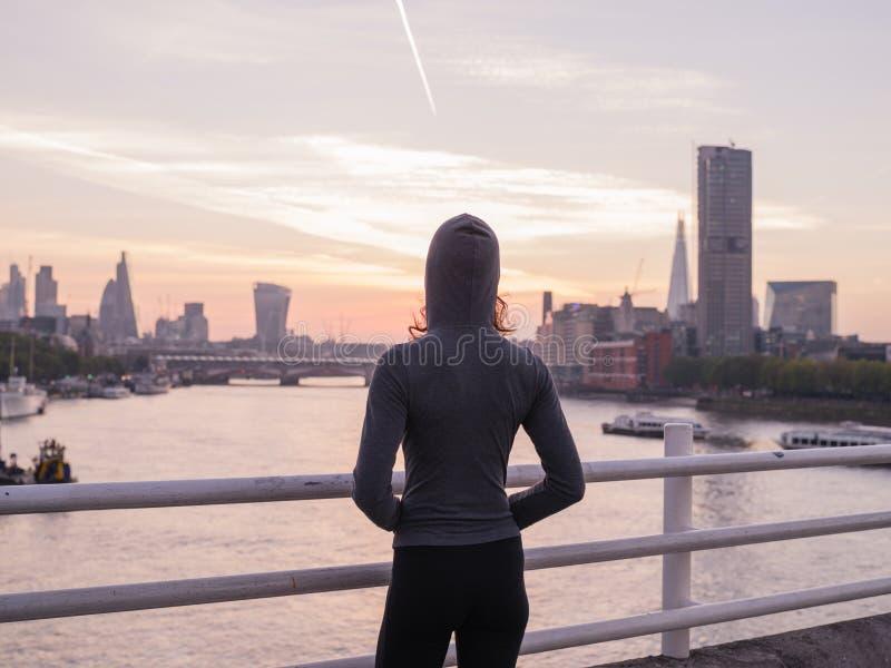 Hoodie vestindo da jovem mulher na ponte em Londres no nascer do sol fotografia de stock royalty free