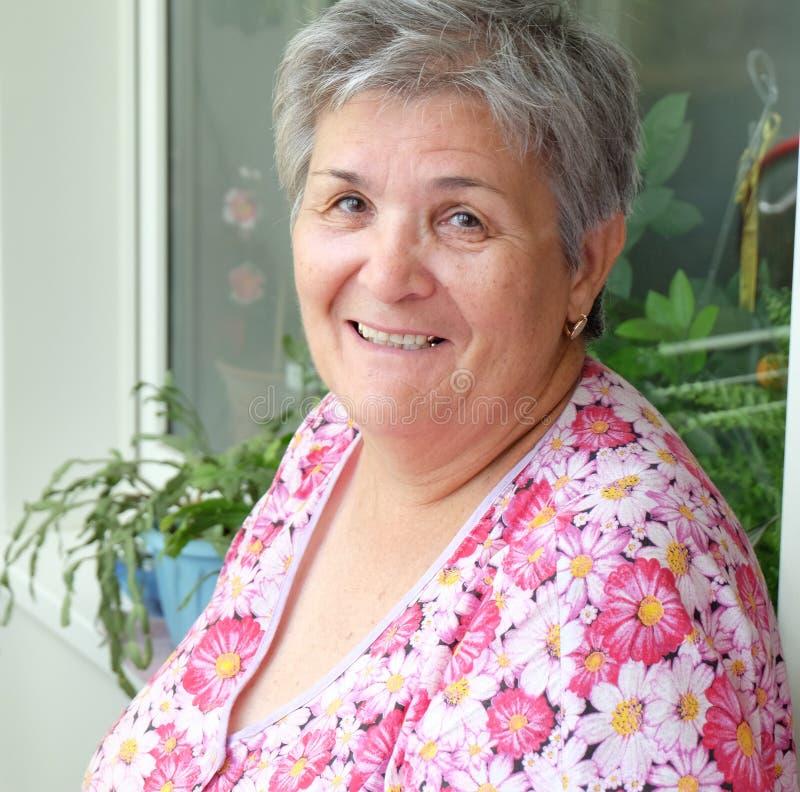 Hoofd en schoudersbeeld van hogere vrouwen in het kleurrijke kleding glimlachen stock foto