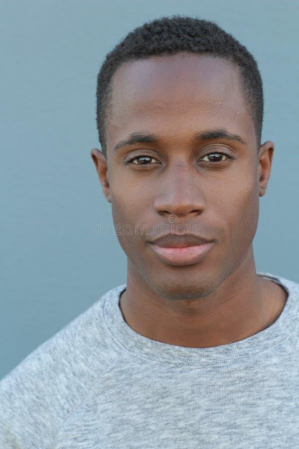 Hoofd en schoudersportret van een knappe Afrikaanse Amerikaanse mens op een blauwe achtergrond royalty-vrije stock afbeeldingen
