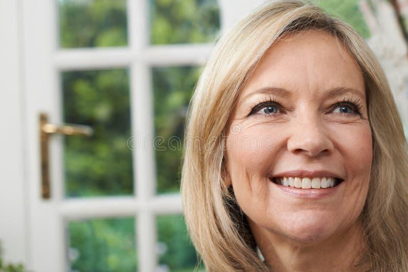 Hoofd en Schoudersportret van Glimlachende Rijpe Vrouw thuis stock foto