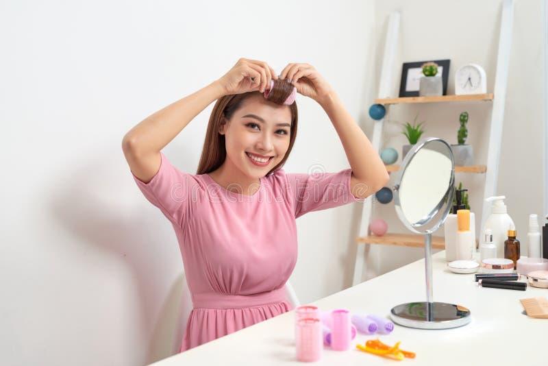 Hoofd en schoudersportret van mooie Aziatische vrouw die haarkrulspelden dragen die in spiegel met brede glimlach, huisbinnenland royalty-vrije stock foto