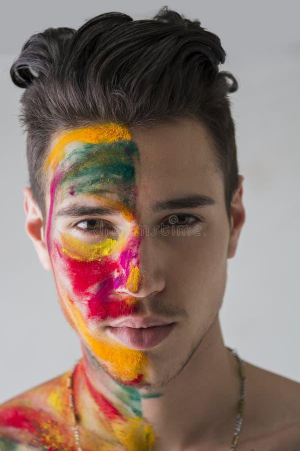 Hoofd-geschoten van de aantrekkelijke jonge die mens, huid met Holi-kleuren wordt geschilderd stock afbeeldingen