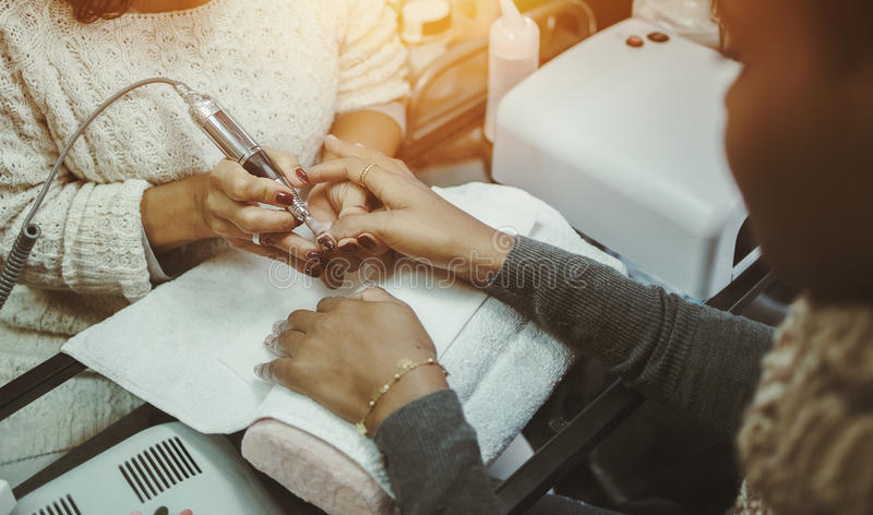 Hoofd het voorbereidingen treffen spijkers van afromeisje voor manicure stock foto's