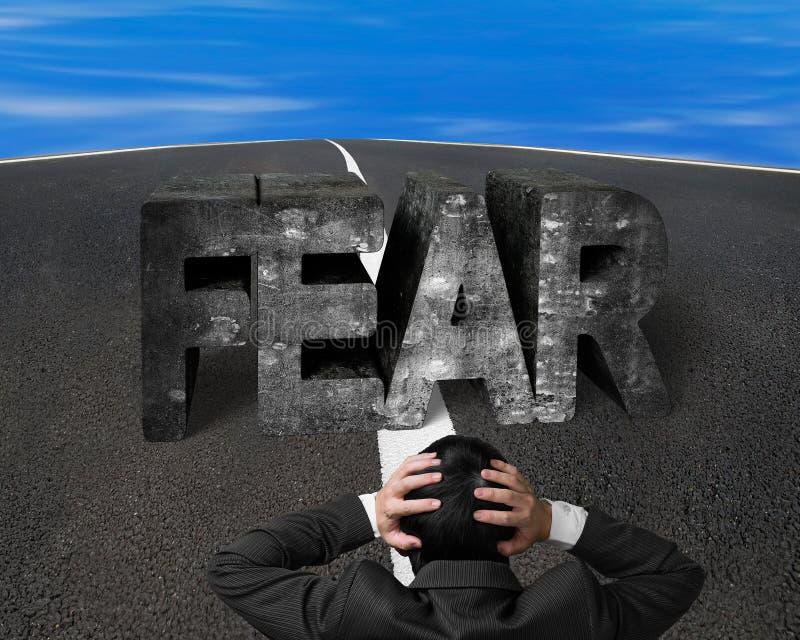 Hoofd onder ogen ziend de vrees concreet woord van de zakenmanholding op asfalt ro stock fotografie