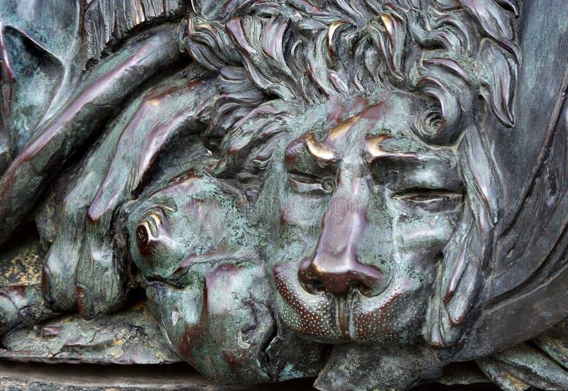 Hoofd van een bronsleeuw bronsbeeldhouwwerk van een slaapleeuw op het monument van glorie in Poltava, de Oekraïne stock afbeeldingen