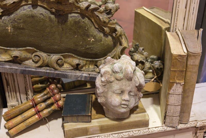 Hoofd van Steenstandbeeld op Houten Lijst dichtbij Antieke Boeken stock afbeeldingen