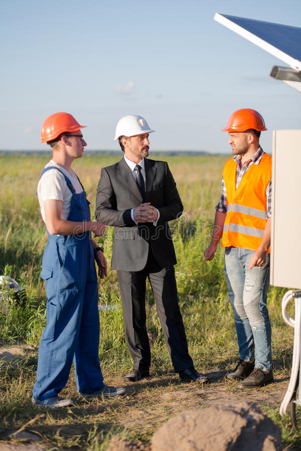 Hoofd van zonne-energiepost die aan ingenieurs spreken stock afbeeldingen