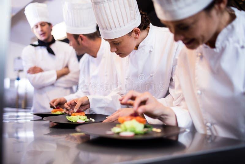 Hoofdchef-kok die andere chef-kok overzien die schotel voorbereiden stock foto