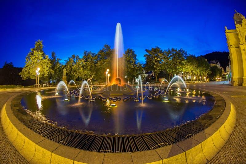 Hoofdcolonnade in de kleine stad Marianske Lazne Marienbad van het het westen Boheemse kuuroord en zingende fontein bij nacht - T stock foto's