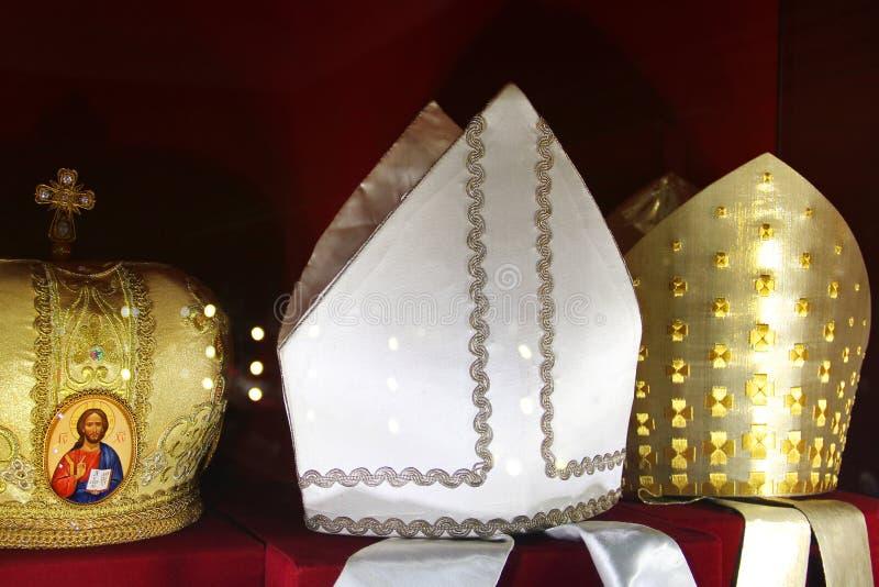 Hoofddeksels van priesters op een rode achtergrond stock afbeelding