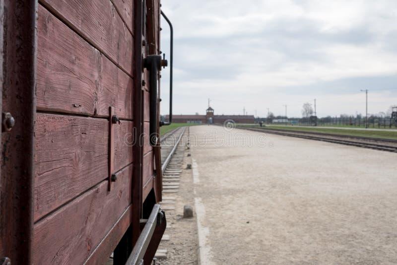 Hoofdingang aan Auschwitz Birkenau die Nazi Concentration Camp dat, één van de veeauto's worden gebruikt tonen om slachtoffers aa stock afbeelding