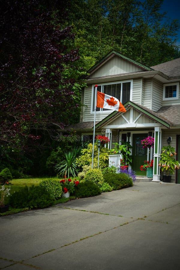 Hoofdingang van familiehuis met Canadese vlag vooraan Donker grenzenbeeld stock fotografie